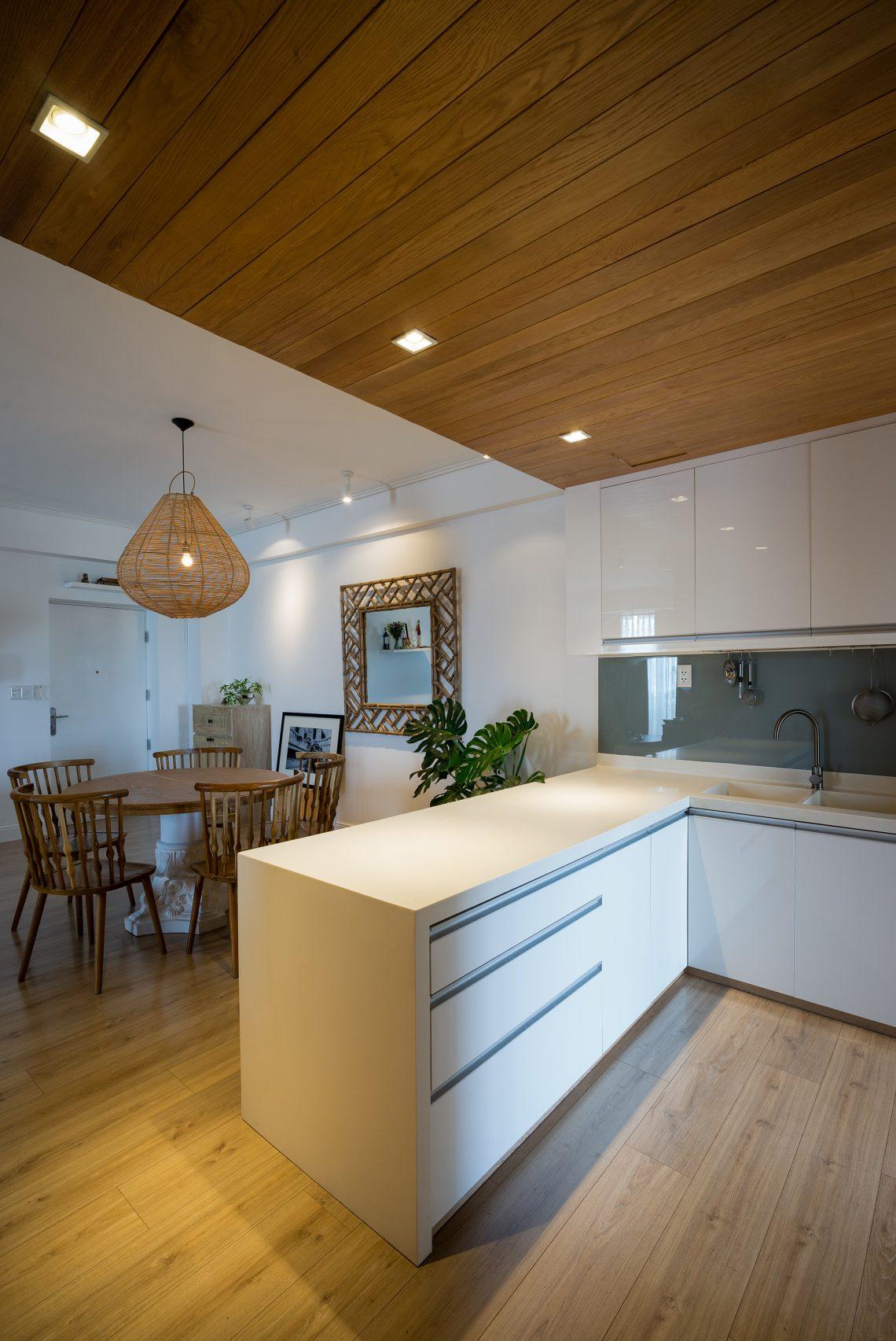 Phòng bếp được ngăn với góc dùng bữa bởi đảo bếp trắng cùng tông màu tủ bếp.