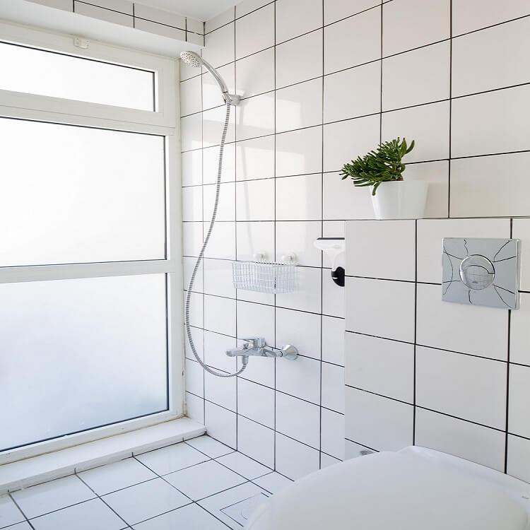 Tường xung quanh và sàn của phòng tắm được ốp gạch men, đơn giản nhưng sạch sẽ.